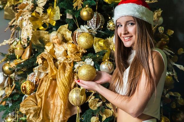 Jovem engraçada linda modelo com olhos escuros, cabelo castanho e chapéu de papai noel, comemorando o ano novo em casa. decoração de ano novo, com emoção positiva posando e olhando para a câmera. decoração de ouro amarelo ..