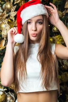 Jovem engraçada linda modelo com olhos escuros, cabelo castanho e chapéu de papai noel, comemorando o ano novo na