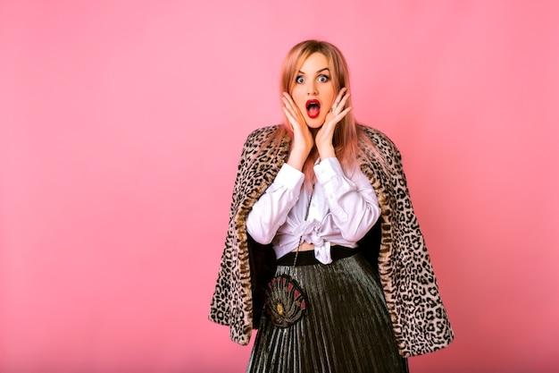 Jovem engraçada surpresa chocada mulher posando em fundo rosa, vestindo camisa branca e casaco de leopardo, emoções poderosas.
