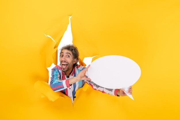 Jovem engraçado apontando para uma página em branco com espaço livre em um buraco rasgado em papel amarelo