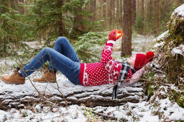 Jovem engraçado com chapéu vermelho na floresta de inverno