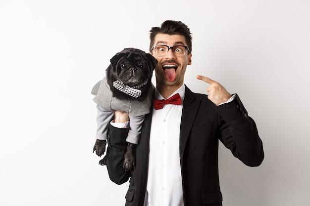 Jovem engraçado em traje de festa, mostrando a língua e fazendo caretas, apontando para o lindo cachorro preto com roupas de inverno, em pé sobre um fundo branco.