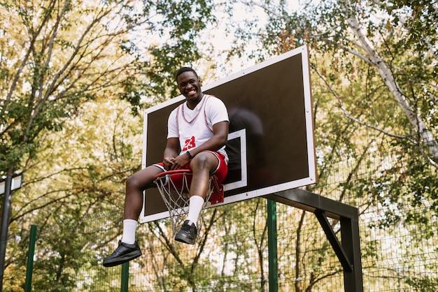 Jovem engraçado jogador de basquete afro-americano em uma camiseta branca e shorts vermelhos se senta em uma cesta na quadra de basquete. ato louco de um jovem jogador de basquete negro. conceito de esportes, moda.