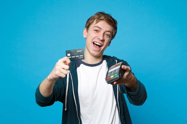 Jovem engraçado segurando o terminal de pagamento do banco moderno sem fio para processar e adquirir pagamentos com cartão de crédito isolados na parede azul. emoções sinceras de pessoas, conceito de estilo de vida.