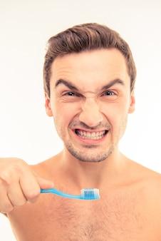 Jovem engraçado segurando uma escova de dentes