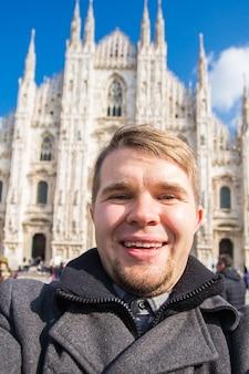 Jovem engraçado tomando selfie perto da catedral de milão, duomo milano, itália.