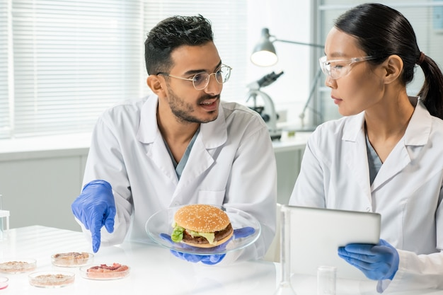 Jovem enluvado com hambúrguer no prato apontando para uma das amostras de carne vegetal crua enquanto descreve suas características para um colega
