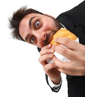 Jovem enquanto come rapidamente um sanduíche