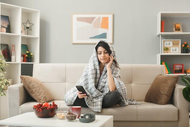 Jovem enrolada em um manto segurando e olhando para o telefone, sentada no sofá atrás da mesa de centro na sala de estar