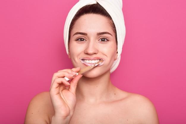 Jovem enrolada toalha branca, limpando os dentes, parece feliz, fazendo procedimentos de manhã no banheiro