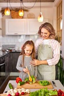 Jovem ensina a filha a misturar salada de vegetais frescos em uma cozinha moderna e iluminada