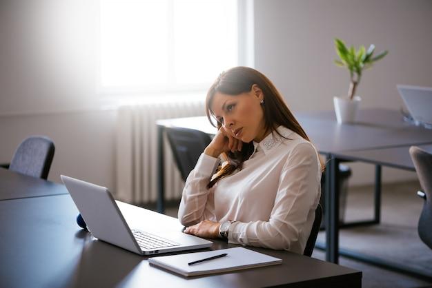 Jovem entediada no escritório trabalhando com um laptop