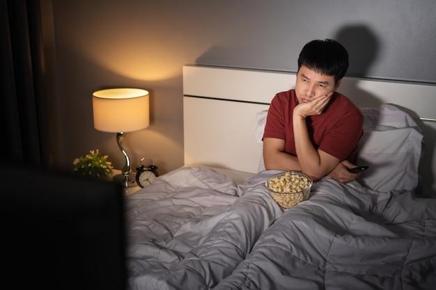 Jovem entediado assistindo tv na cama à noite