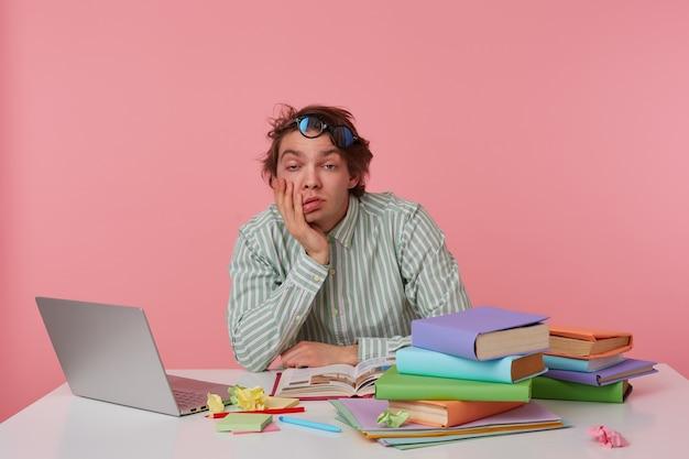 Jovem entediado de óculos, sentado a uma mesa com livros, trabalhando em um laptop, parece com sono, usa uma camisa em branco, olha cansado para a câmera isolada sobre fundo rosa.