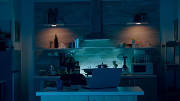 Jovem entrando na cozinha segurando um celular dando comando de voz para o aplicativo de casa inteligente e as luzes acendendo