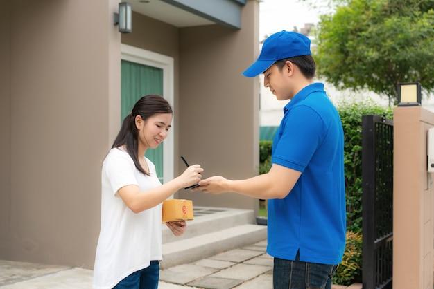 Jovem entrega asiática no sorriso uniforme azul e segurando a pilha de caixas de papelão na frente de casa