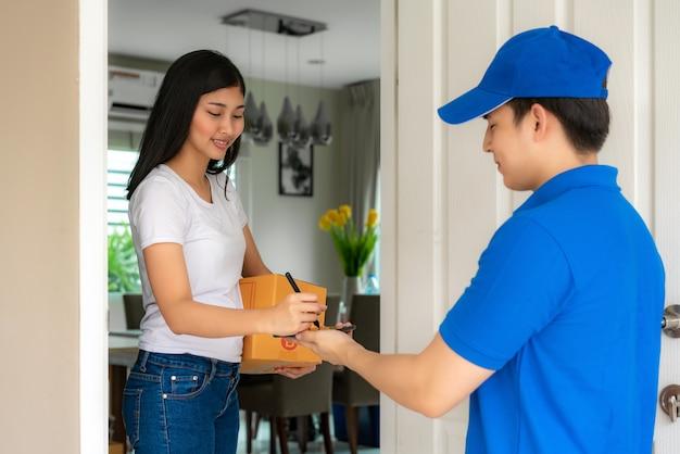 Jovem entrega asiática no sorriso uniforme azul e segurando o smartphone na frente de casa