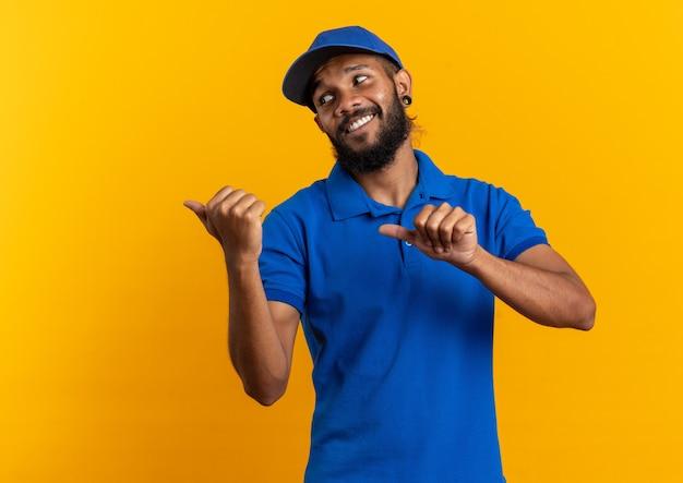 Jovem entregador afro-americano sorridente, olhando e apontando para o lado isolado em um fundo laranja com espaço de cópia