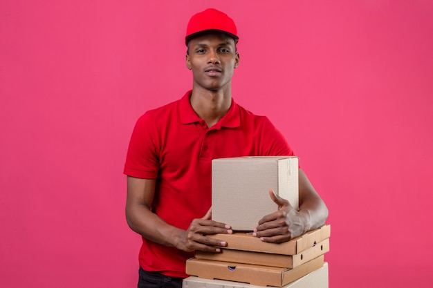 Jovem entregador americano africano vestindo camisa polo vermelha e boné com pilha de caixas, olhando para a câmera sobre rosa isolado