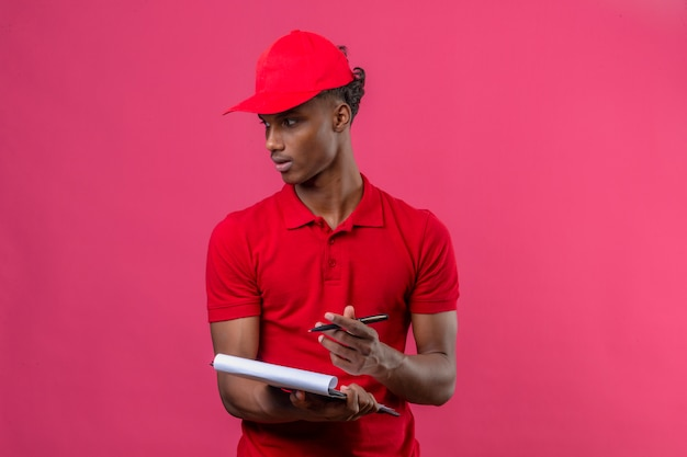 Jovem entregador americano africano vestindo camisa polo vermelha e boné escrevendo na área de transferência, olhando para longe para o lado sobre rosa isolado