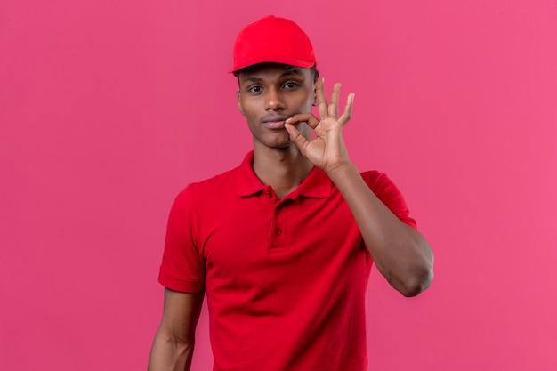 Jovem entregador americano africano vestindo camisa polo vermelha e boné mostrando um sinal de fechar o gesto de silêncio boca sobre rosa isolado