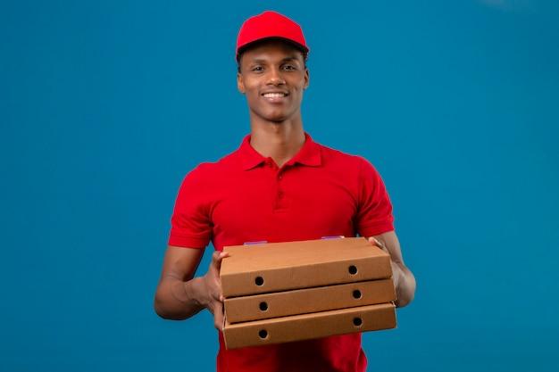 Jovem entregador americano africano vestindo camisa polo vermelha e boné segurando a pilha de caixas de pizza com um grande sorriso sobre azul isolado
