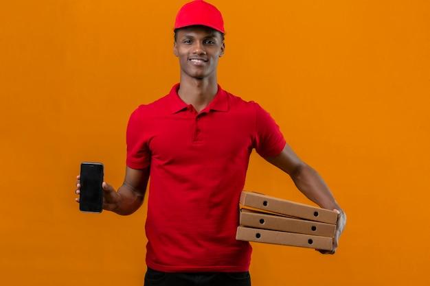 Jovem entregador americano africano vestindo camisa polo vermelha e boné segurando a pilha de caixas de pizza e mostrando o smartphone na mão para a câmera com sorriso no rosto sobre laranja isolado