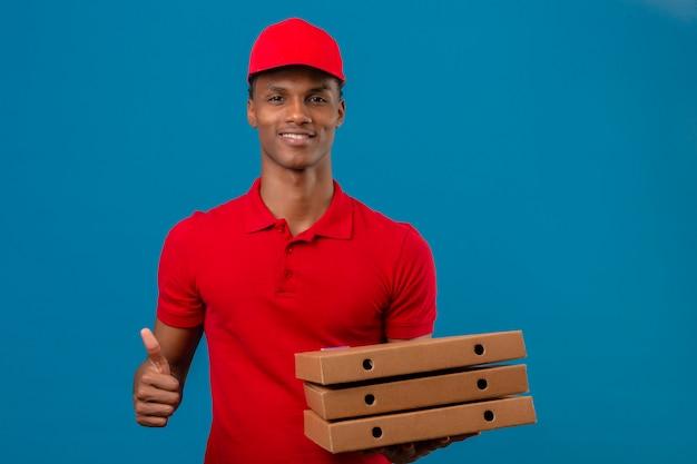Jovem entregador americano africano vestindo camisa polo vermelha e boné segurando a pilha de caixas de pizza, mostrando os polegares para cima e sorrindo sobre azul isolado