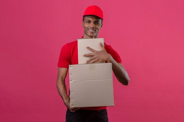 Jovem entregador americano africano vestindo camisa polo vermelha e boné segurando a pilha de caixas, olhando para a câmera com sorriso no rosto sobre rosa isolado