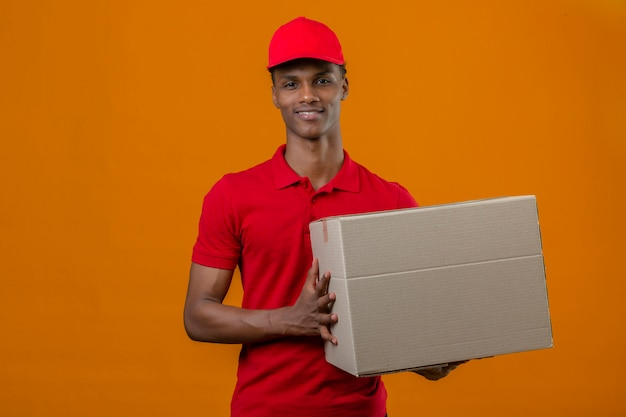 Jovem entregador americano africano vestindo camisa polo vermelha e boné segurando o pacote caixa com sorriso no rosto sobre laranja isolado