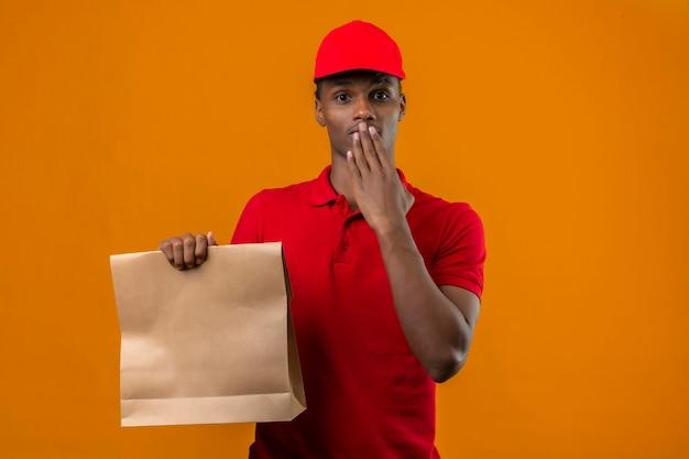 Jovem entregador americano africano vestindo camisa polo vermelha e boné segurando o saco de papel com comida para viagem cobrindo a boca com a mão olhando surpreso sobre laranja isolado