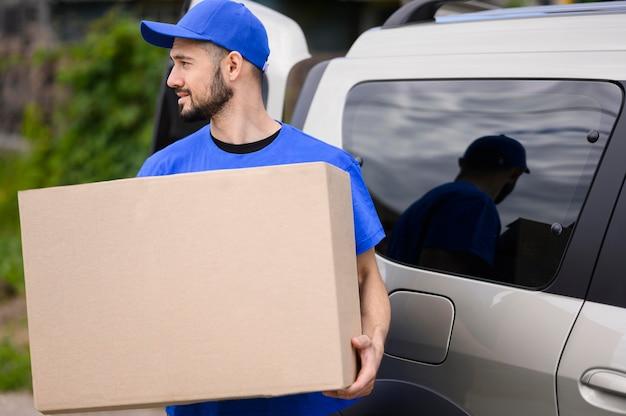 Jovem entregador carregando caixa de papelão