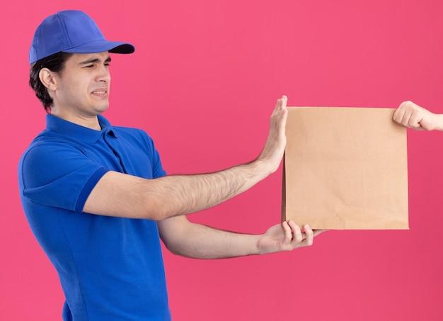 Jovem entregador caucasiano, carrancudo, de uniforme azul e boné