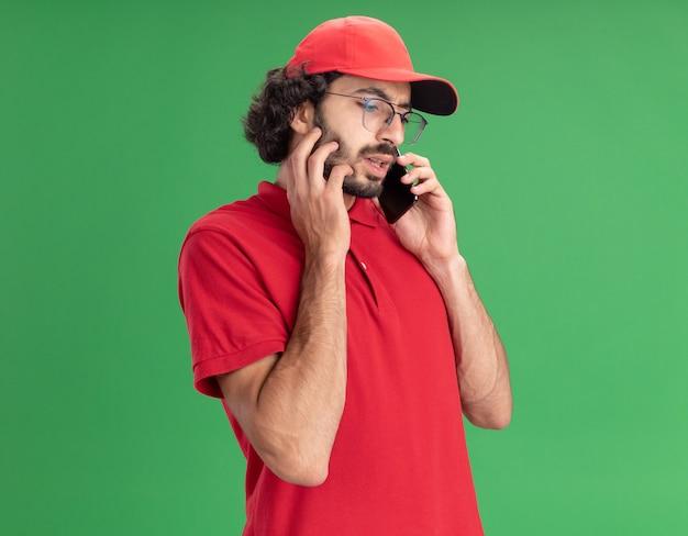 Jovem entregador caucasiano, carrancudo, de uniforme vermelho e boné usando óculos, tocando o rosto, olhando para baixo, falando no telefone isolado na parede verde com espaço de cópia