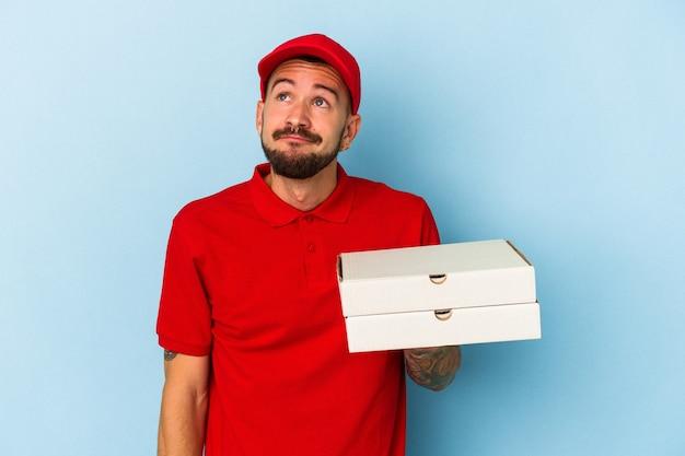 Jovem entregador, caucasiano, com tatuagens, segurando pizzas isoladas em um fundo azul, sonhando em alcançar objetivos e propósitos