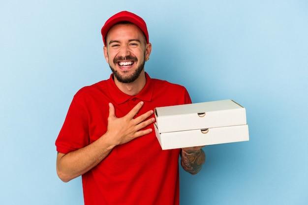 Jovem entregador caucasiano com tatuagens segurando pizzas isoladas no fundo azul ri alto, mantendo a mão no peito.