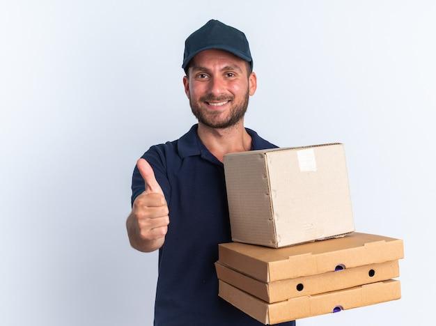 Jovem entregador caucasiano com uniforme azul e boné segurando pacotes de pizza e uma caixa de papelão, olhando para a câmera, mostrando o polegar isolado na parede branca com espaço de cópia.