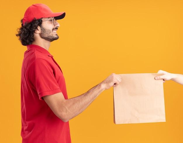 Jovem entregador caucasiano com uniforme vermelho e boné, sorrindo, em pé na vista de perfil, dando um pacote de papel para o cliente, olhando para o cliente