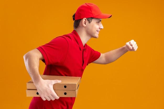 Jovem entregador caucasiano de camisa vermelha sorridente, de pé de lado e segurando caixas de pizza fingindo correr