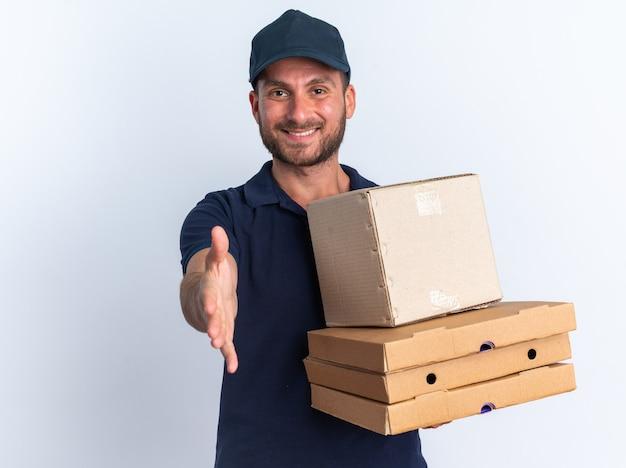 Jovem entregador caucasiano de uniforme azul sorridente e boné segurando pacotes de pizza e uma caixa de papelão, olhando para a câmera, fazendo gesto de saudação isolado na parede branca com espaço de cópia