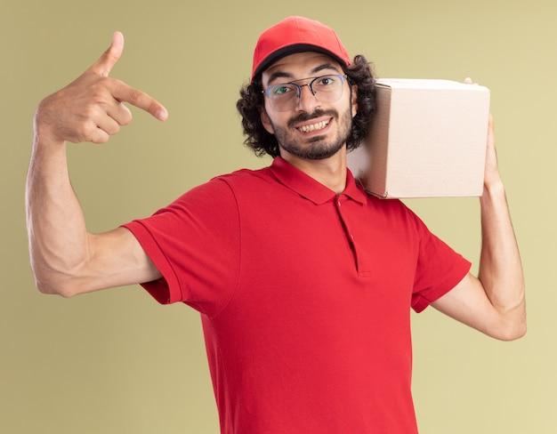 Jovem entregador caucasiano de uniforme vermelho e boné de óculos, segurando uma caixa de papelão no ombro, olhando e apontando isolado na parede verde oliva.