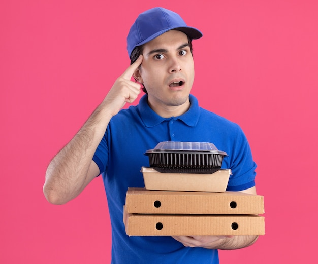 Jovem entregador, caucasiano, impressionado, de uniforme azul e boné, segurando pacotes de pizza com um recipiente para comida e um pacote de comida de papel sobre eles, fazendo o gesto de pensar isolado na parede rosa