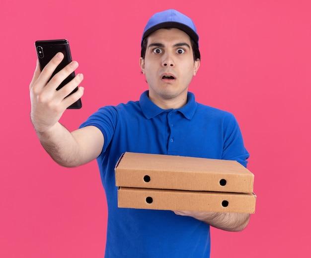 Jovem entregador, caucasiano, impressionado, de uniforme azul e boné, segurando pacotes de pizza estendendo-se no celular