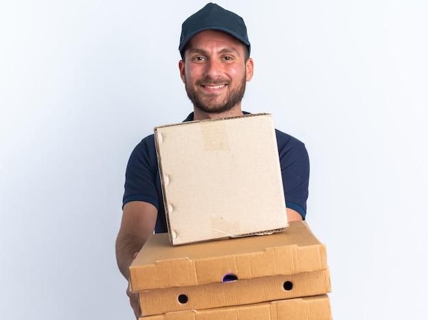 Jovem entregador caucasiano sorridente com uniforme azul e boné esticando a caixa de papelão e os pacotes de pizza em direção à câmera