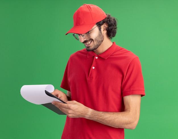 Jovem entregador caucasiano sorridente, de uniforme vermelho e boné, usando óculos, de pé na vista de perfil, segurando e olhando para a prancheta, apontando o dedo sobre ela