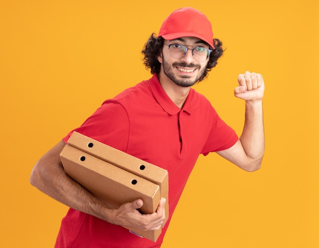 Jovem entregador caucasiano, sorridente, de uniforme vermelho e boné, usando óculos, em vista de perfil, segurando pacotes de pizza, fazendo gesto de bater