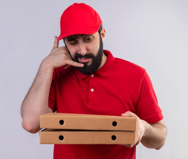 Jovem entregador caucasiano vestindo uniforme vermelho e boné, segurando e olhando para caixas de pizza e fazendo gesto de chamada, isolado no fundo branco