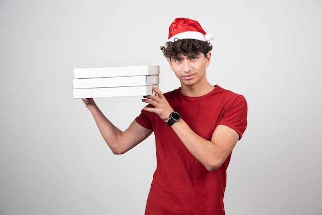 Jovem entregador com caixas de pizza em pé