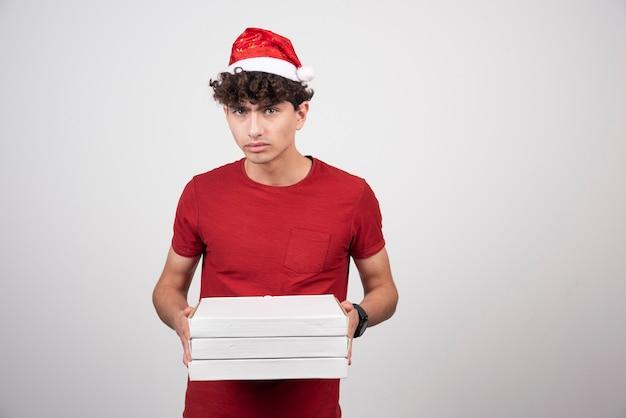 Jovem entregador com caixas de pizza