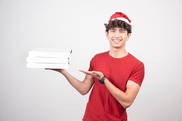 Jovem entregador com chapéu de papai noel segurando caixas de pizza.
